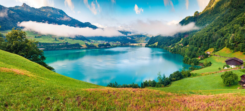 Lungerersee湖有雾的夏天全景  瑞士阿尔卑斯山脉,龙疆五颜六色的早晨视图村庄地点,瑞士,欧洲 库存照片