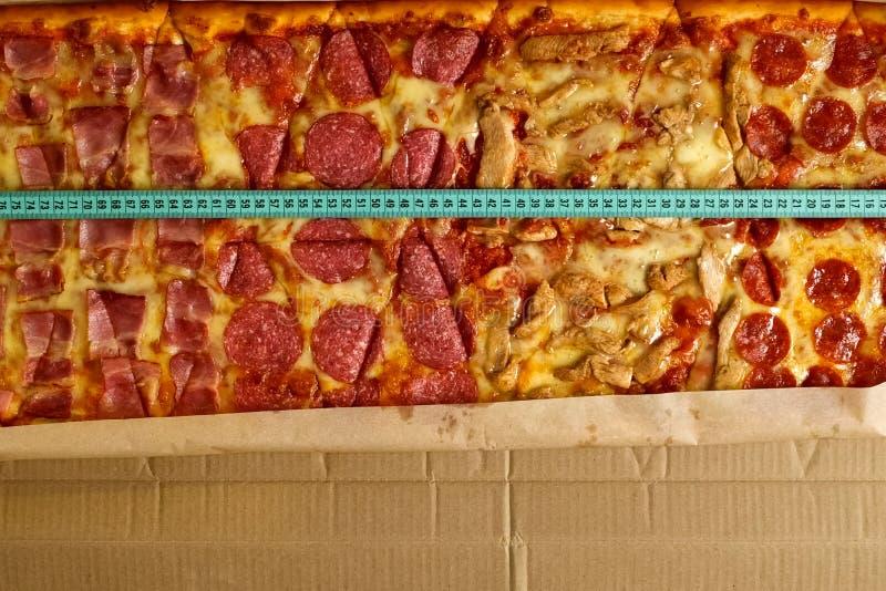 Lunghezza della pizza di misura con una misura di nastro immagini stock
