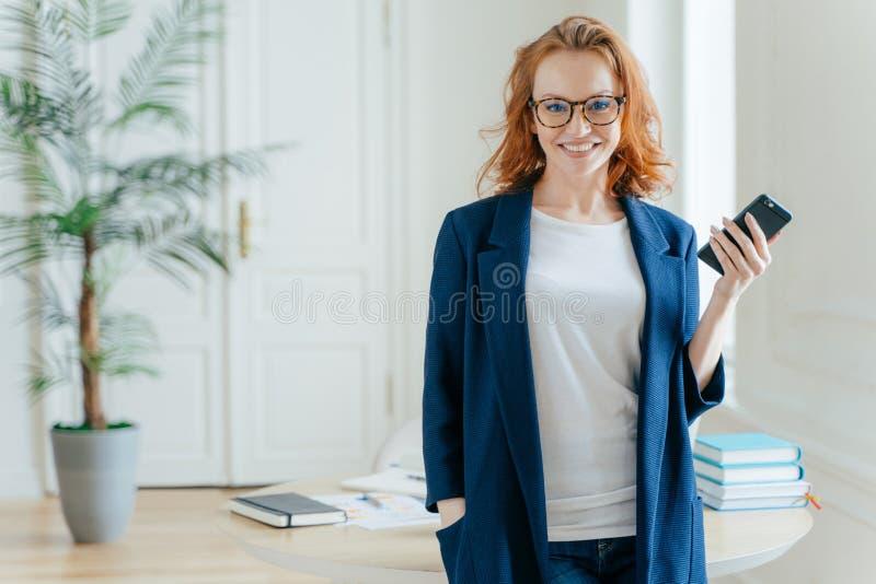 Lunghezza di metà sparata di cellulare moderno di bei usi della donna per il blogging nelle reti sociali, pose nell'interno dell' immagine stock
