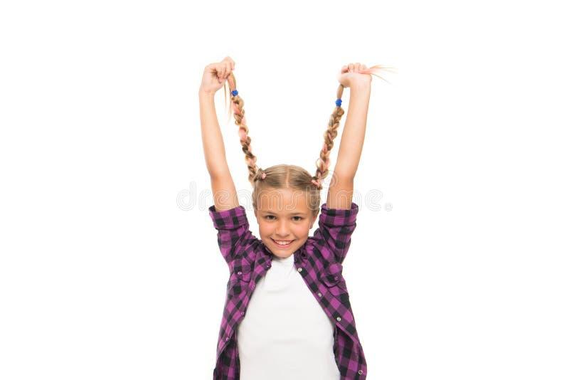 Lungo e intrecciato Una ragazza felice tiene le trecce bionde lunghe Sorrisetto di bambino adorabile con capelli lunghi Capelli l immagini stock