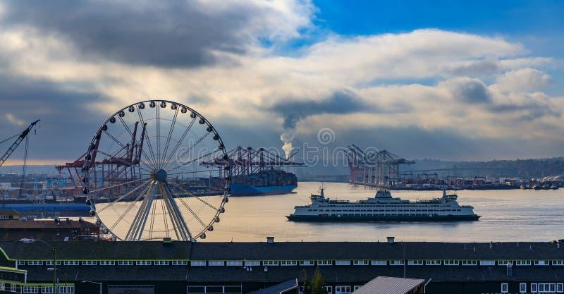 Lungomare di SeattleSeattle con la grande ruota e Puget Sound con un traghetto che tira in immagine stock libera da diritti