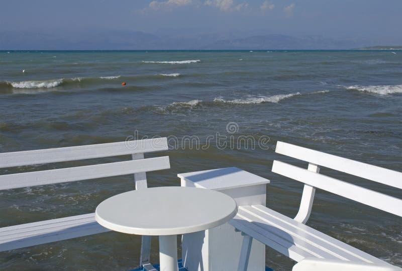 Lungonmare con la tavola ed il banco fotografie stock libere da diritti