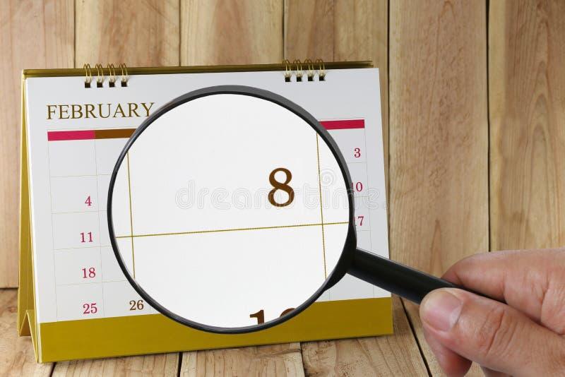 Lupa à disposição no calendário você pode olhar o oitavo dia imagens de stock royalty free