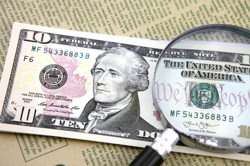 Lupa con diez dólares en el periódico imagen de archivo libre de regalías
