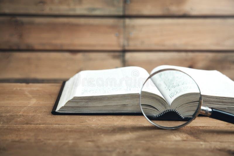 Lupa con el libro en la tabla de madera Busque y descubra foto de archivo