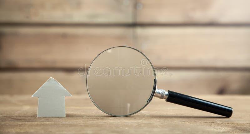 Lupa con la casa en fondo de madera Inspecci?n de la propiedad foto de archivo