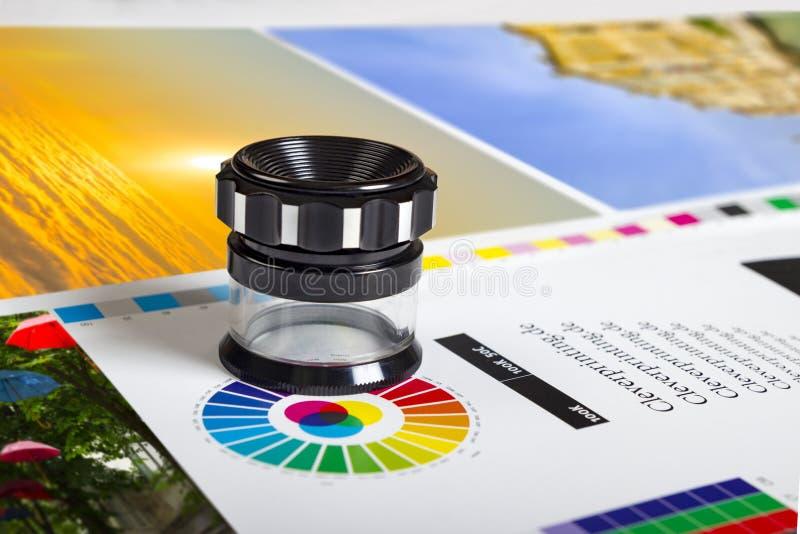 Lupa de la impresión en la hoja impresa compensada con colores básicos foto de archivo libre de regalías