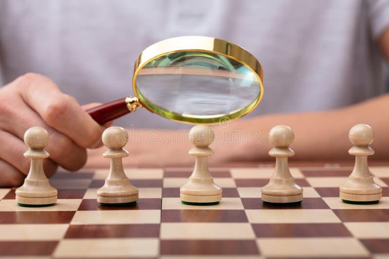 Lupa de la tenencia del hombre sobre pedazo de ajedrez del empe?o foto de archivo