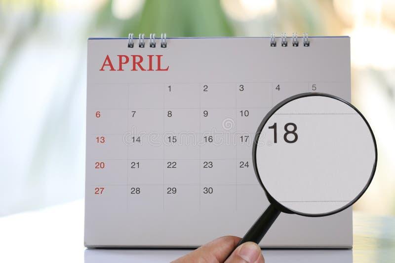 Lupa a disposición en calendario usted puede mirar dieciocho días fotografía de archivo