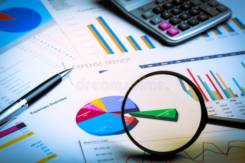 Lupa e calculadora em gráficos de negócio imagens de stock