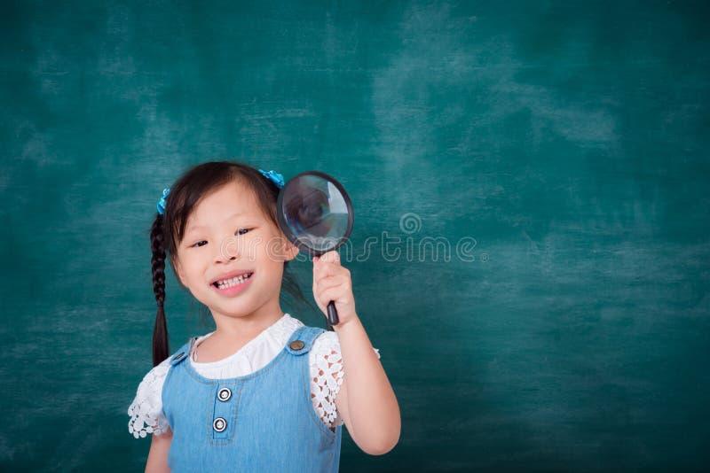 Lupa e sorrisos da terra arrendada da menina fotografia de stock royalty free