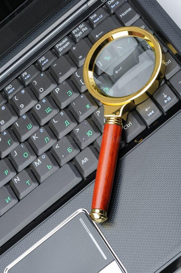 Lupa e um portátil foto de stock royalty free