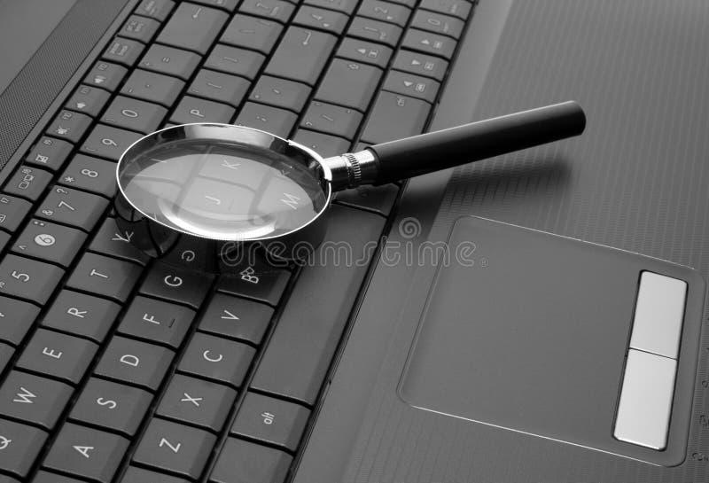 Lupa en el ordenador portátil imagen de archivo