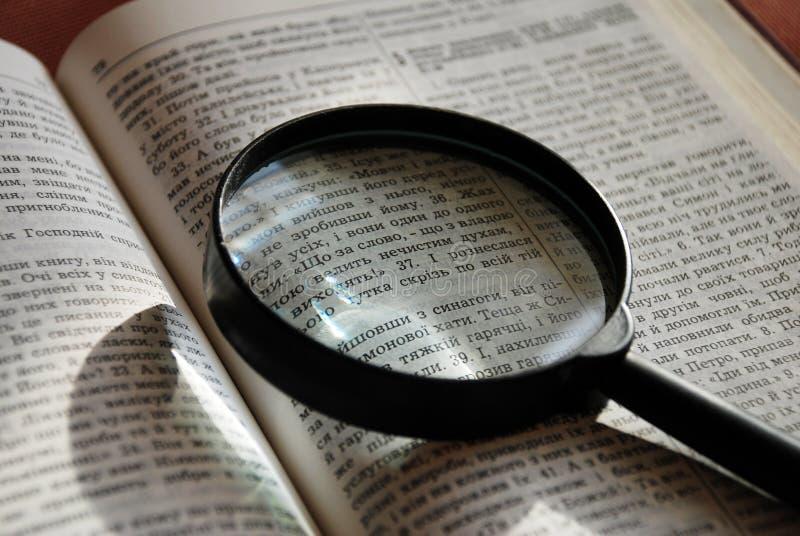 Lupa en la página ucraniana de la biblia fotos de archivo libres de regalías