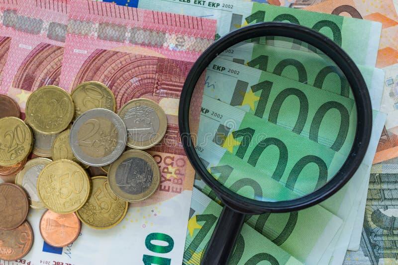 Lupa en la pila de billetes de banco euro con las monedas euro como fi imagen de archivo libre de regalías