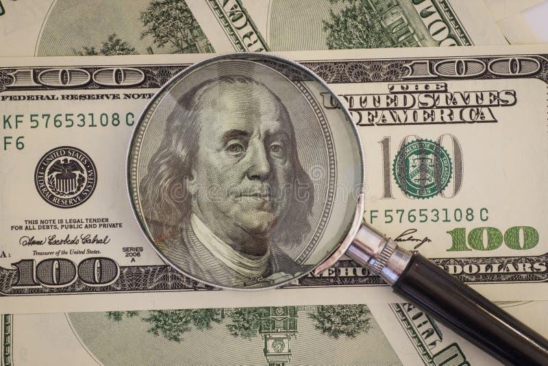 A lupa encontra-se em cem notas de dólar imagem de stock