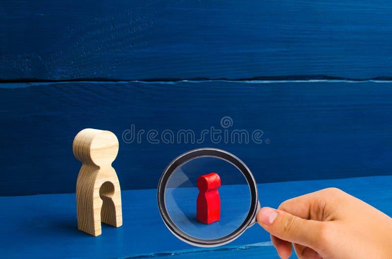 A lupa está olhando a figura de madeira de uma mulher com um vácuo sob a forma de uma criança dentro dos suportes do corpo e olha fotos de stock