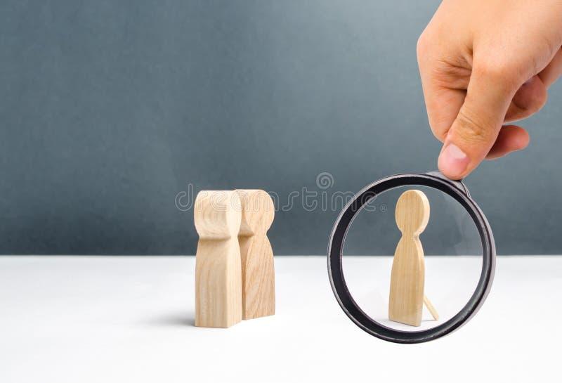 A lupa está olhando a figura humana falsa perto de duas figuras humanas que olham a decepção e mosheynik imagem de stock