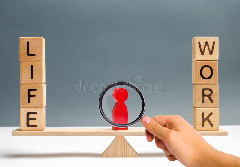 A lupa está olhando a figura humana vermelha entre a vida das palavras e o trabalho nas escalas escolha entre a vida e o trabalho imagem de stock royalty free