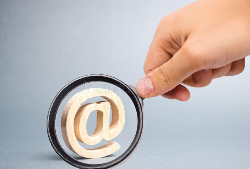 A lupa est? olhando o ?cone do e-mail no fundo cinzento Correspond?ncia do Internet, uma comunica??o no Internet contatos imagem de stock