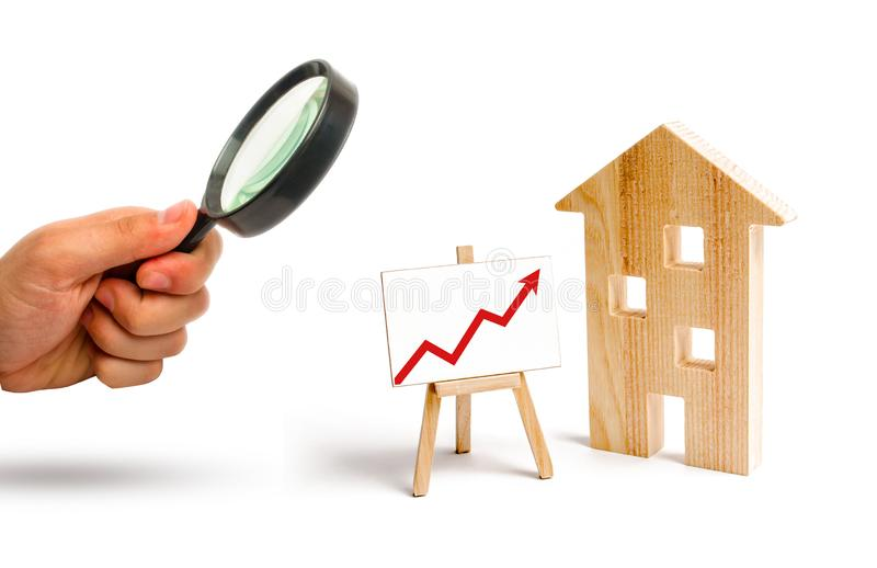 A lupa está olhando o suporte de madeira da casa com seta vermelha acima Aumento da procura para o abrigo e bens imobiliários fotografia de stock