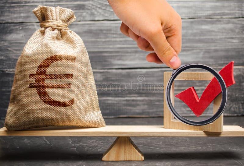 A lupa está olhando um saco com euro- dinheiro e uma marca de verificação vermelha de uma voz em escalas Intervenção no político foto de stock royalty free