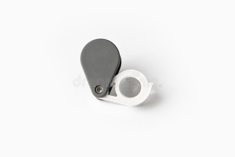 A lupa para diamantes ou vê o amuleto isolado em um fundo branco imagem de stock
