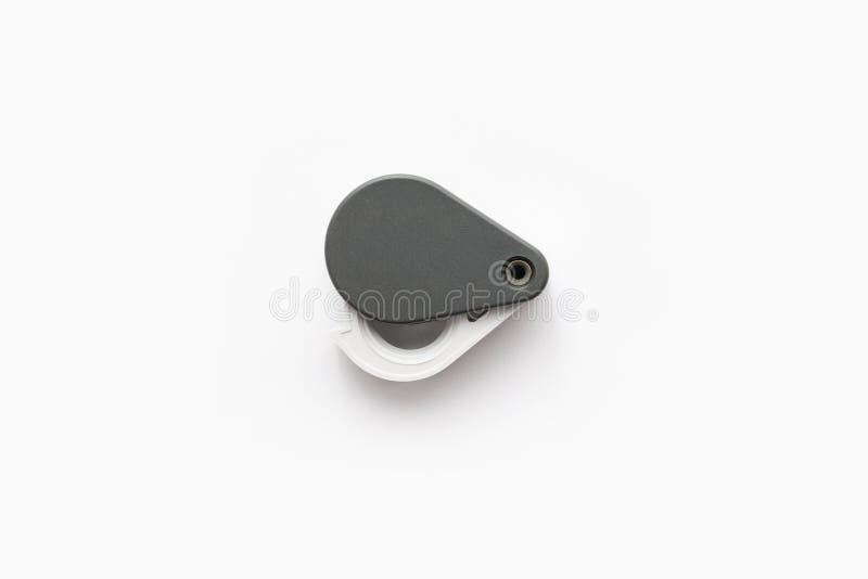 A lupa para diamantes ou vê o amuleto isolado em um fundo branco fotografia de stock