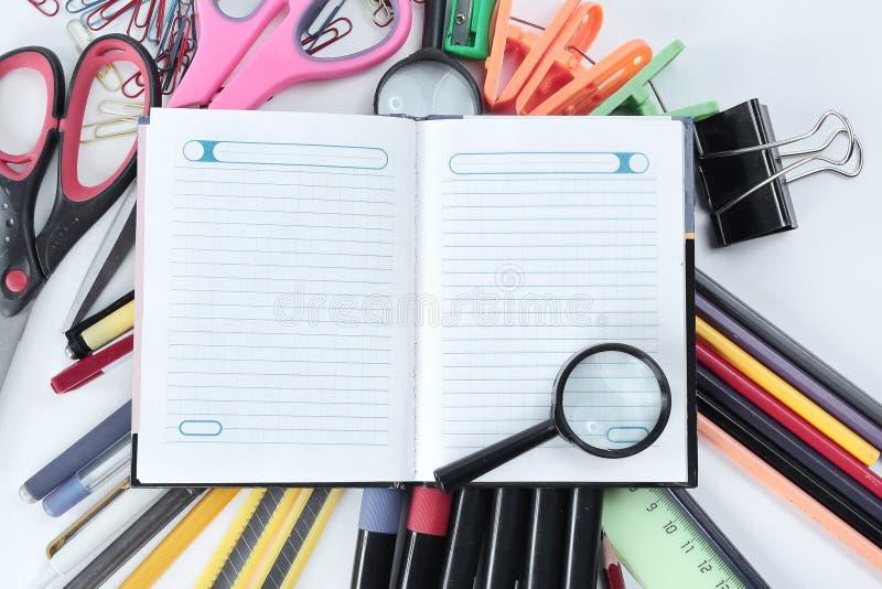 Lupa, planificador del día y materiales de oficina en el fondo blanco Foto con el espacio de la copia imagenes de archivo