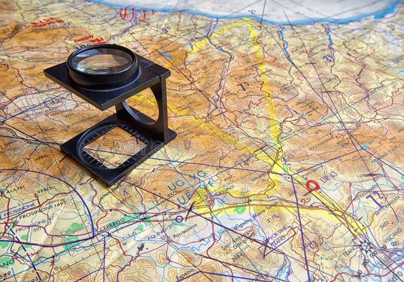 Lupa plegable en mapa del vuelo fotografía de archivo