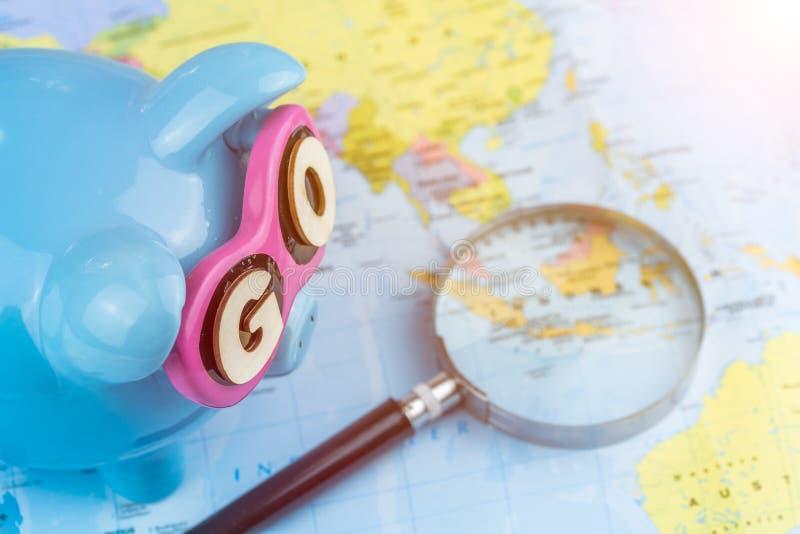 Lupa que pone en el mapa defocused La hucha del ahorro está lista para el viaje VA el lema en las gafas de sol fotos de archivo libres de regalías
