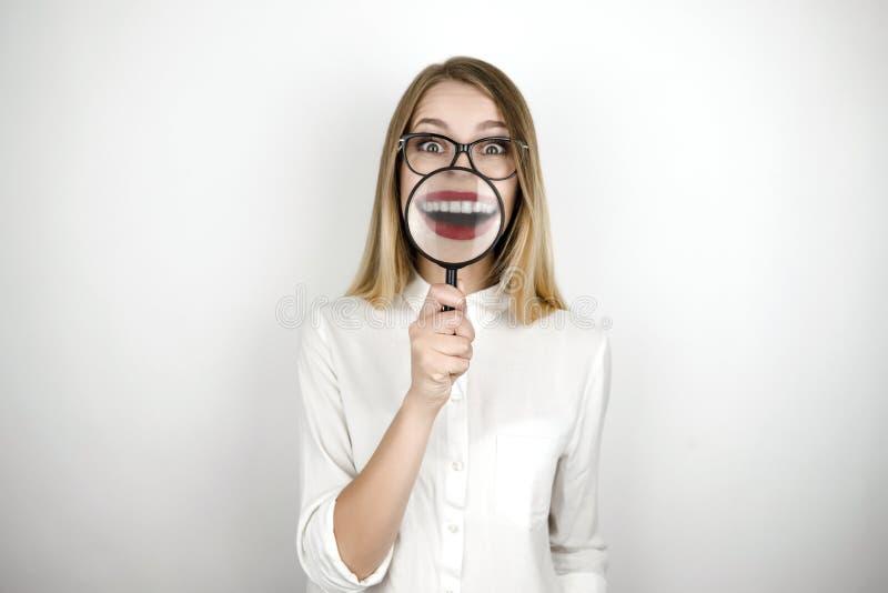 Lupa rubia hermosa joven de la tenencia de la mujer cerca de su fondo blanco aislado boca fotografía de archivo libre de regalías