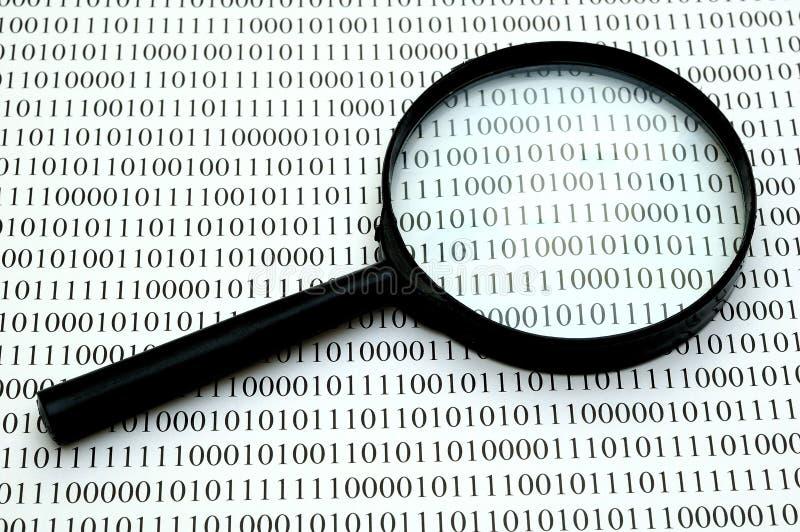 Lupa y código binario imagen de archivo