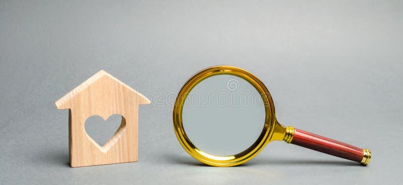 Lupa y casa de madera miniatura Casa que busca concepto Valoraci?n casera Evaluaci?n de la propiedad Opción de la ubicación para foto de archivo