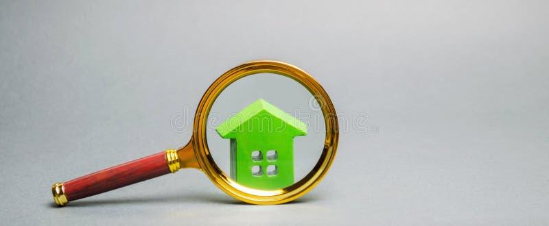 Lupa y casa de madera miniatura Casa que busca concepto Valoraci?n casera Evaluaci?n de la propiedad Opción de la ubicación para fotos de archivo libres de regalías