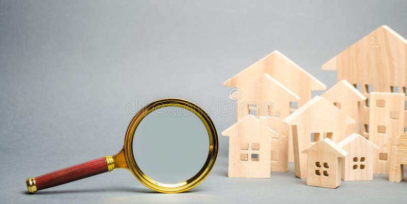 Lupa y casas de madera Casa que busca concepto Valoraci?n casera Evaluaci?n de la propiedad Opción de la ubicación para foto de archivo