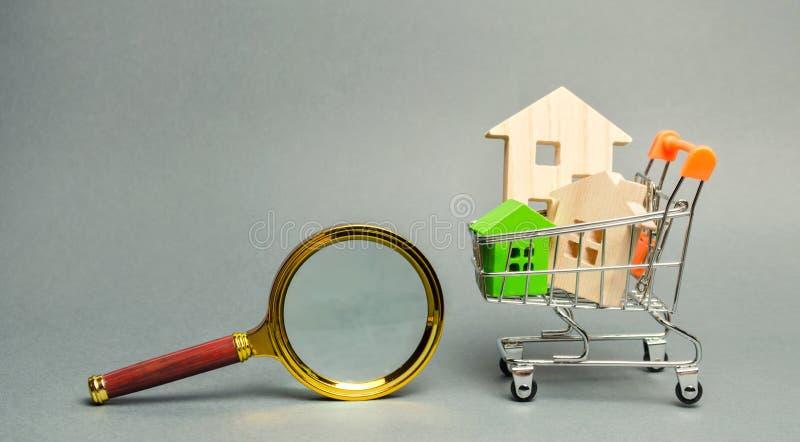 Lupa y casas de madera miniatura Casa que busca concepto Valoraci?n casera Evaluaci?n de la propiedad Opción de la ubicación para fotografía de archivo libre de regalías
