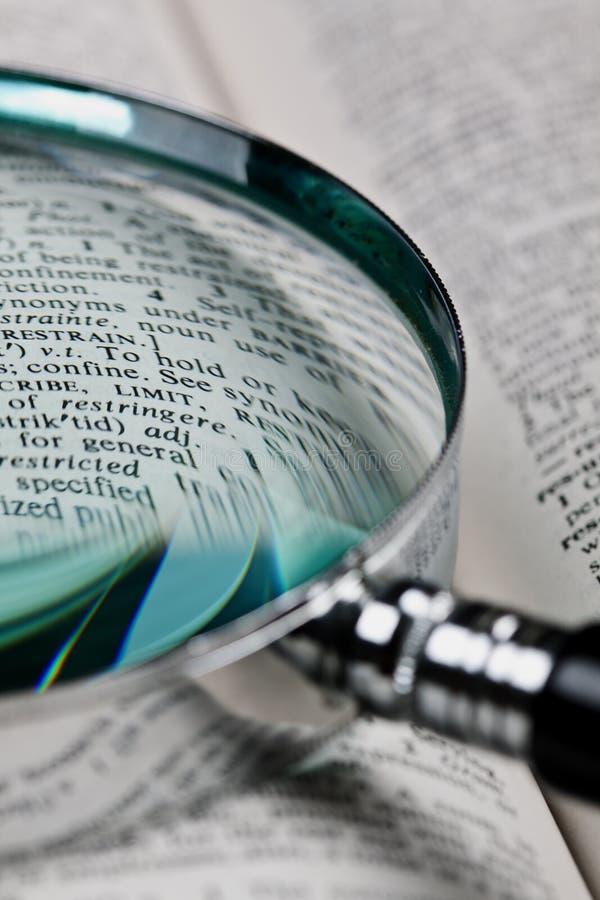 Lupa y diccionario imagenes de archivo
