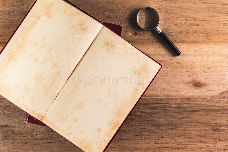 Lupa y pila de libro viejo foto de archivo