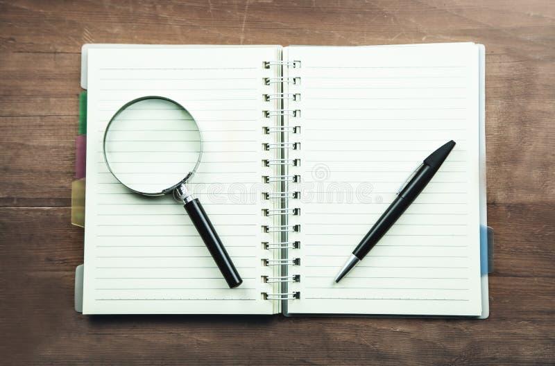 Lupa y pluma en la libreta Concepto del asunto foto de archivo libre de regalías