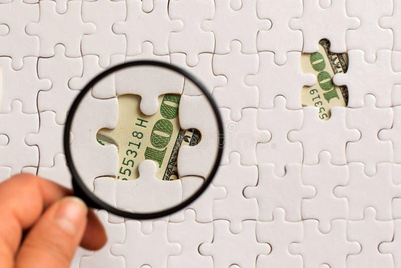 Lupa y rompecabezas blanco en cientos dólares de billetes de banco foto de archivo