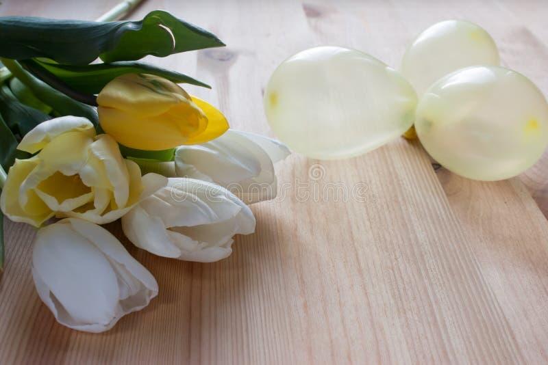 Lupans blancos y amarillos, pequeños globos amarillos en un fondo de madera ligero imagen de archivo