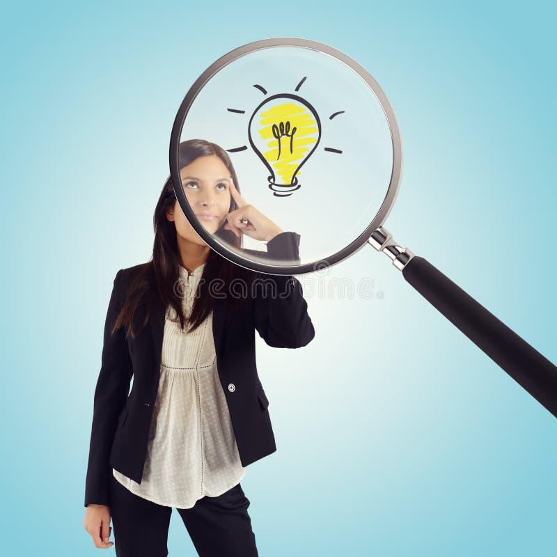 Lupe überprüft die Idee einer jungen Geschäftsfrau stockbild