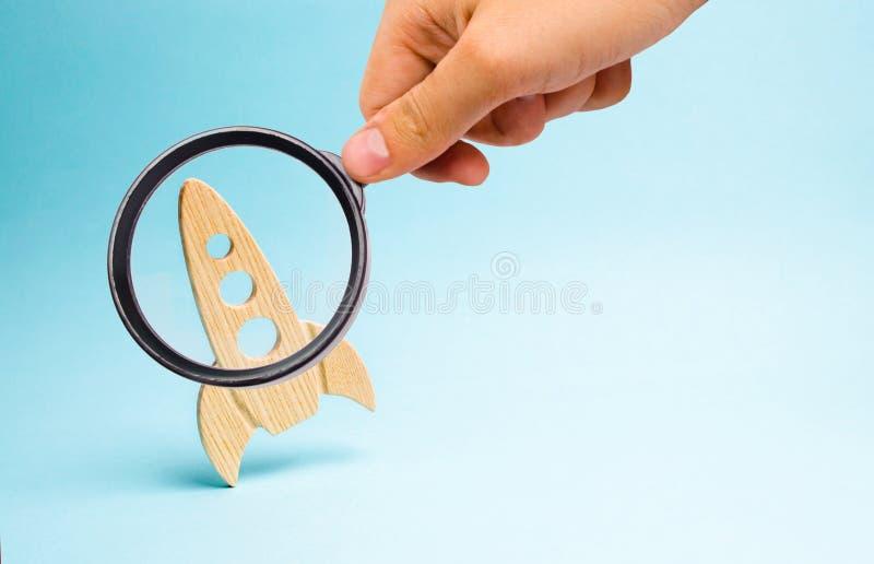 Lupe betrachtet das Rocket auf einem blauen Hintergrund Konzept eines Starts, der Ausbildung und des Wunsches zu erforschen platz stockfotografie