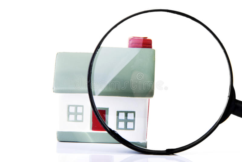 Lupe, die ein Haus kontrolliert. lizenzfreies stockbild