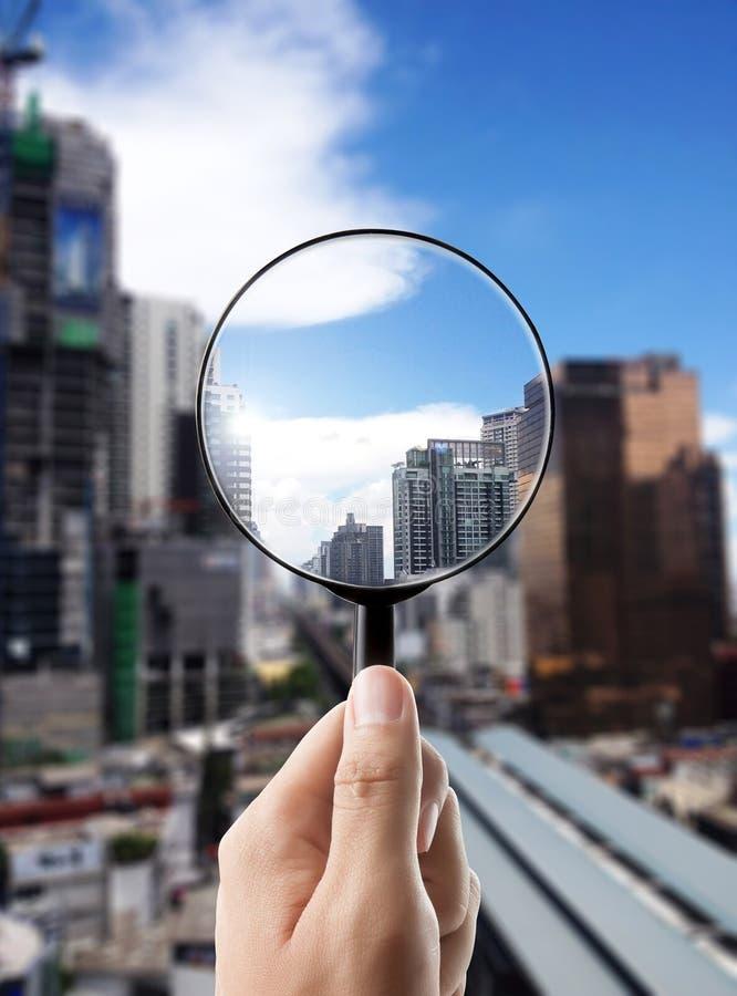 Lupe und Stadtbild im Fokus stockfotografie