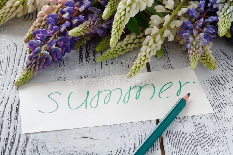 Lupine цветет с карточкой сообщения на старом деревянном столе стоковое фото