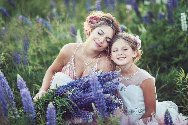 Lupine blommor för moder- och dottersammankomst i härligt fält på solnedgång Härlig flicka i den violetta klänningen som rymmer e arkivbilder