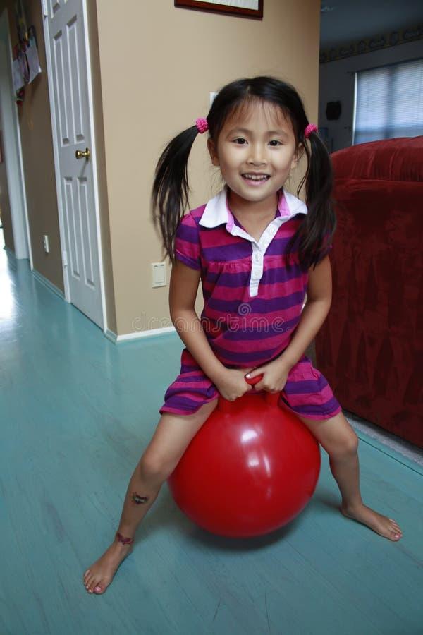 Lupulagem asiática da menina na esfera vermelha imagem de stock royalty free