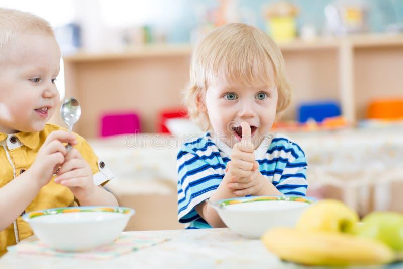 Lura att äta i dagis och uppvisning av tummar upp royaltyfri foto